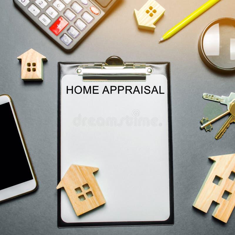 Таблица с деревянными домами, калькулятор, монетки, лупа с оценкой слова домашней Оценка имущества контракта по-настоящему стоковое фото rf