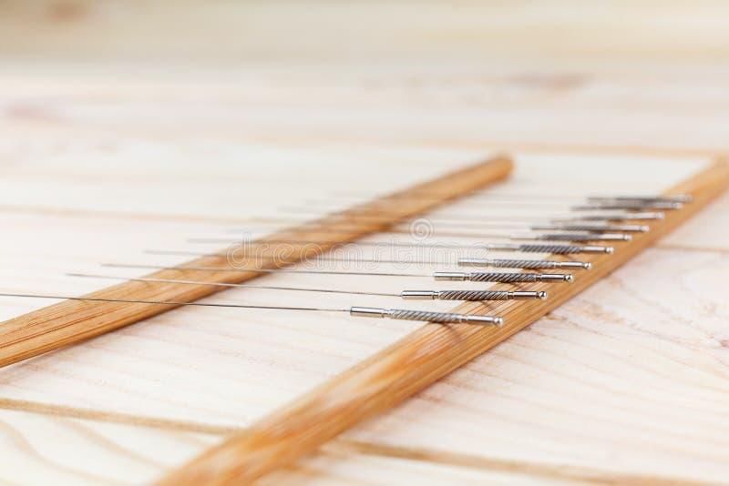 Таблица с иглами для иглоукалывания Серебряные иглы для традиционной медицины иглоукалывания на таблице стоковое фото