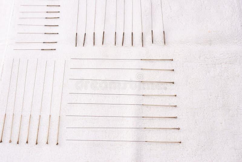 Таблица с иглами для иглоукалывания Серебряные иглы для традиционной медицины иглоукалывания на таблице стоковые изображения rf