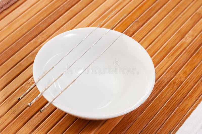 Таблица с иглами для иглоукалывания Серебряные иглы для традиционной медицины иглоукалывания на таблице стоковые изображения