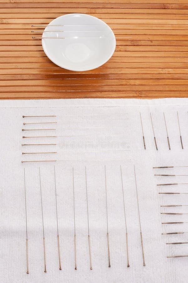 Таблица с иглами для иглоукалывания Серебряные иглы для традиционной медицины иглоукалывания на таблице стоковая фотография rf
