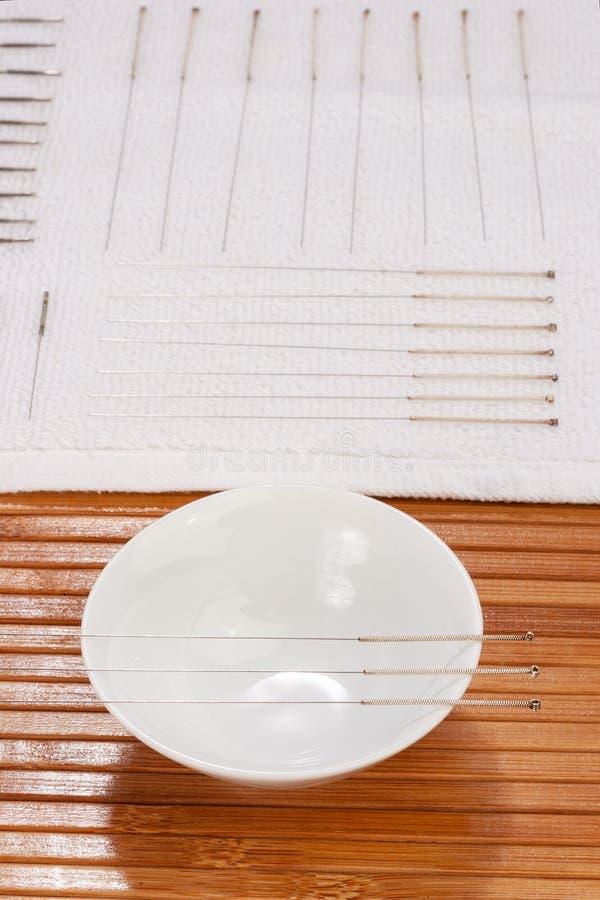 Таблица с иглами для иглоукалывания Серебряные иглы для традиционной медицины иглоукалывания на таблице стоковые фото