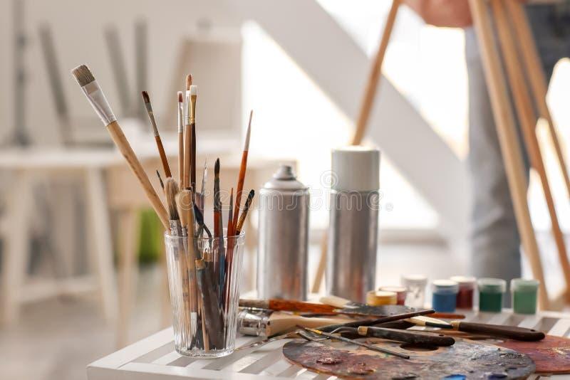 Таблица с инструментами и красками в мастерской художника стоковое фото