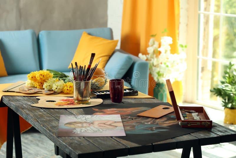 """Таблица с инструментами, красками и изображениями в художнике \ """"мастерской s стоковая фотография"""