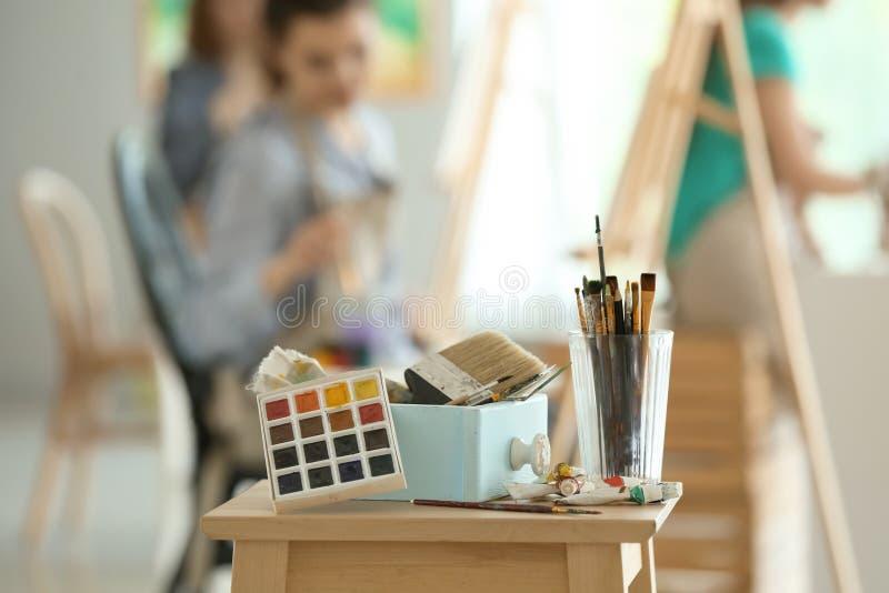 Таблица с красками и инструментами в мастерской художника стоковые фотографии rf