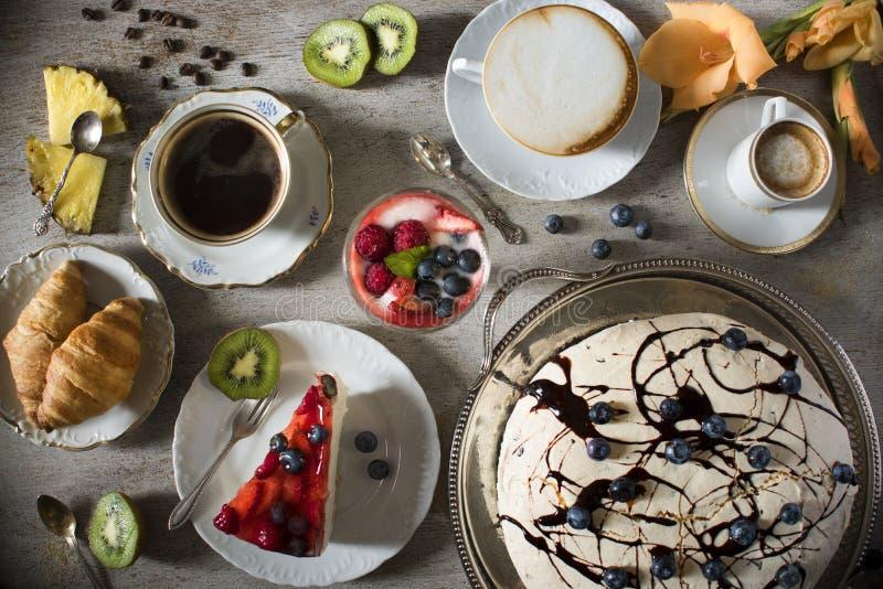 Таблица с нагрузками кофе, тортов, пирожных, печений, cakepops, десертов, плодов, цветков и круассанов стоковое фото