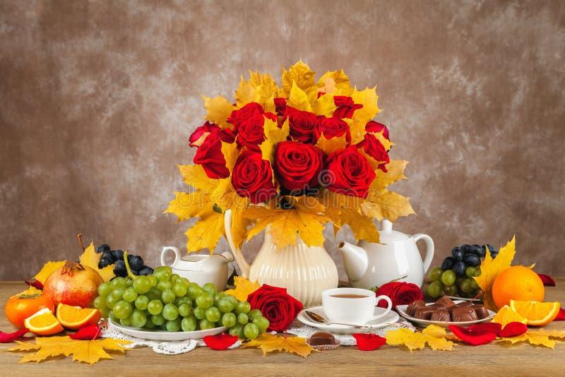 Таблица с чашками чаю, шоколадами и розами букета стоковая фотография
