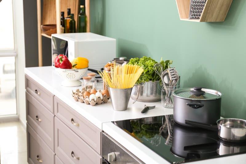 Таблица с kitchenware и продуктами внутри помещения стоковые изображения rf