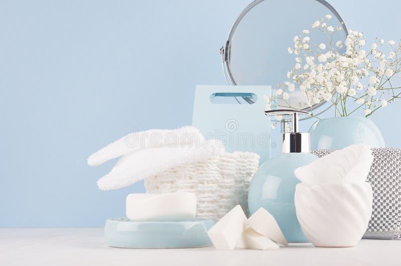 Таблица шлихты с зеркалом круга, косметическими серебряными аксессуарами и белыми небольшими цветками в керамической пастельной г стоковое изображение