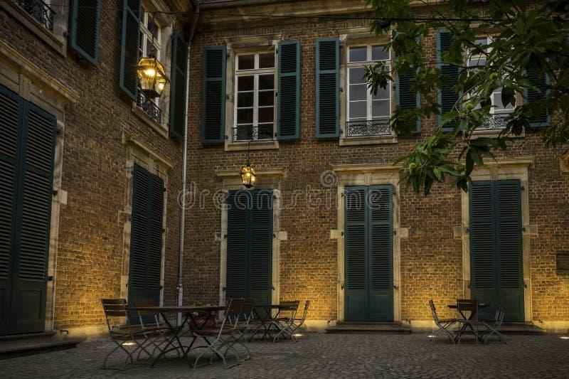 Таблицы и стулья аккуратно уложили вне закрытого здания под тусклыми накаляя laterns стоковое изображение