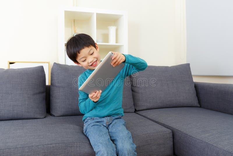 Таблетка игры мальчика Азии стоковая фотография