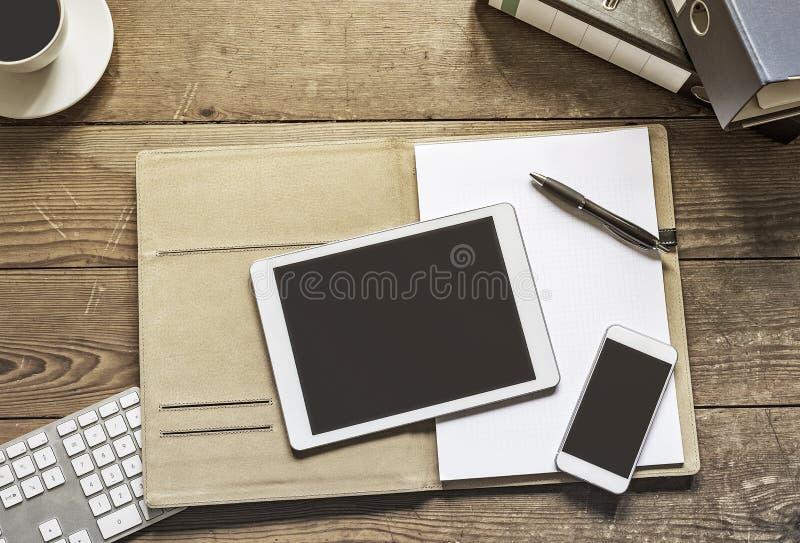 Таблетка и телефон на папке офиса стоковые изображения rf