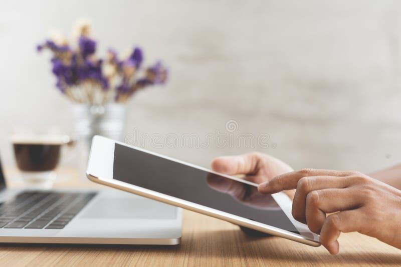Таблетка пользы руки селективного фокуса цифровая на столе работы стоковое изображение