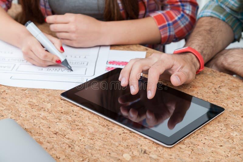 Таблетка руки молодого человека касающая sceen, чертеж женщины стоковая фотография