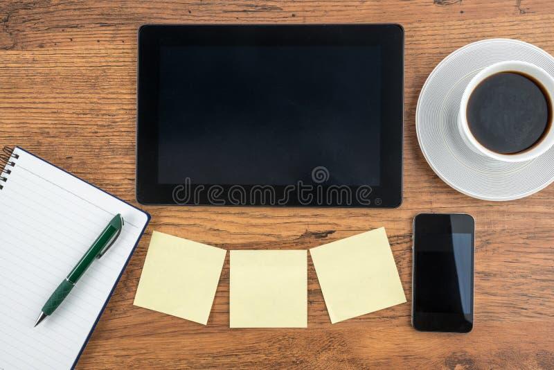 Таблетка, слипчивое примечание, тетрадь и умный телефон с кофе стоковое фото rf