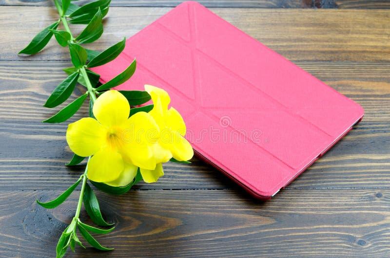 Таблетка с красной крышкой и желтая флора на деревянной земле стоковые изображения