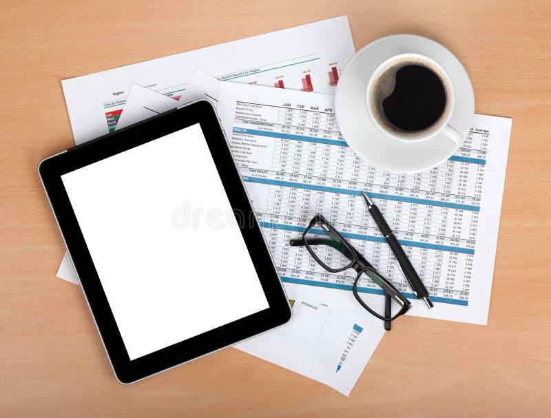 Таблетка с пустым экраном над бумагами с номерами и диаграммами стоковые изображения