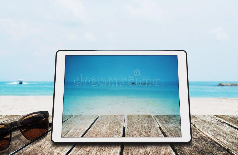 Таблетка цифров с солнечными очками на деревянном столе на тропическом пляже стоковые изображения rf