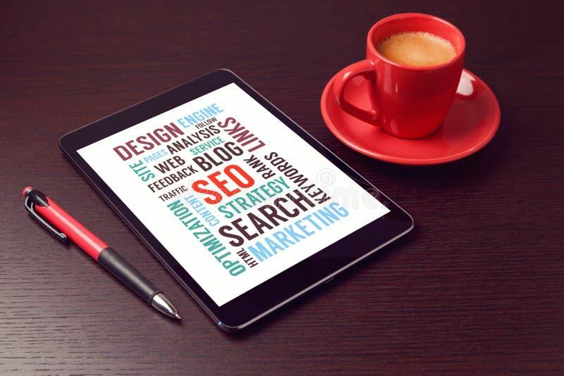 Таблетка цифров с словами SEO и кофейная чашка на столе офиса стоковые изображения rf
