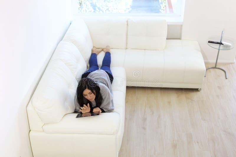 Таблетка чтения лежа на софе стоковое изображение rf
