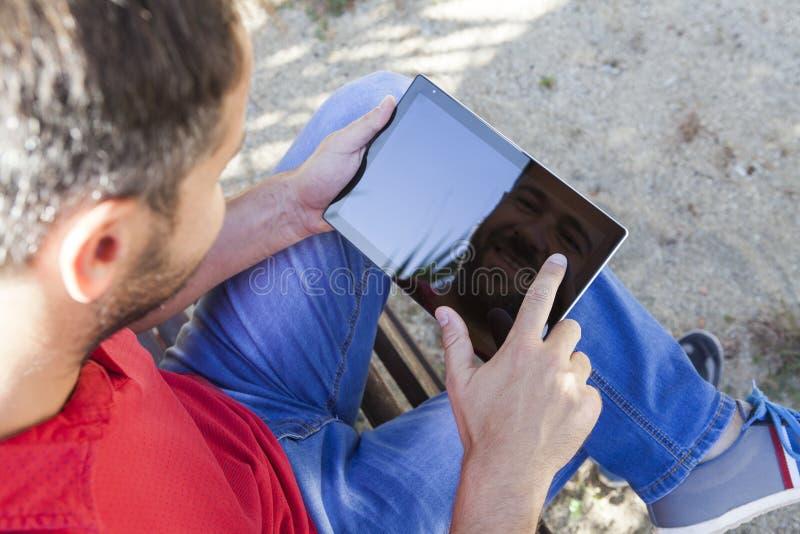 Таблетка чтения человека сидя в стенде стоковая фотография