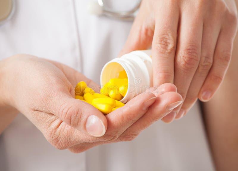 Таблетки доктора лить желтые в ладони стоковое изображение rf