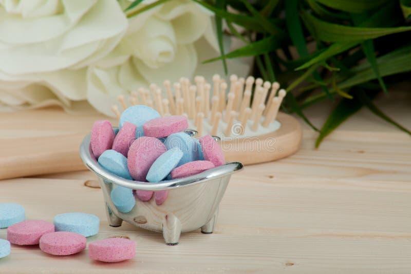 Таблетки цвета времени ванны для детей на деревянной предпосылке стоковая фотография