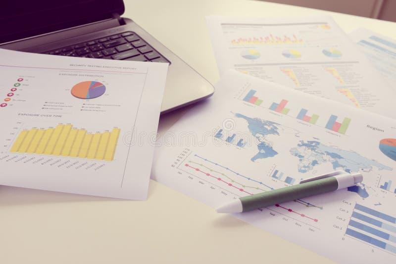 Таблица деятельности бизнесмена с компьтер-книжкой и отчетом стоковые фотографии rf
