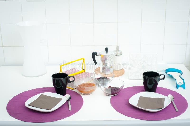 Таблица завтрака установленная в кухне белого света стоковые фото