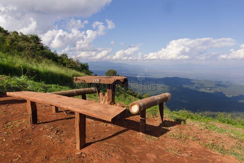 Таблица и стулья с взглядом травы, горы и облачного неба хиа стоковые фото