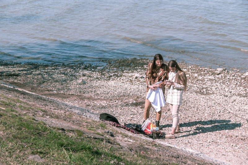 Таганрог, Россия - 07 04 19: 2 маленькой девочки стоят на каменном камешке около моря и взгляде в смартфон стоковое изображение rf