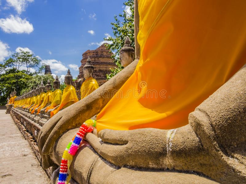 Таиланд, впечатляющая строка статуй Будды с оранжевыми робами в виске Ayutthaya старом стоковое фото