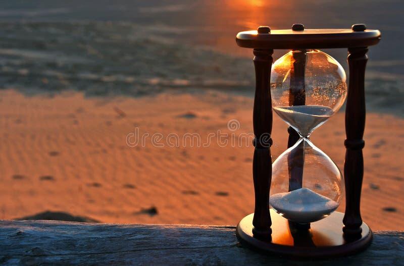 Таймер песка с заревом захода солнца стоковое фото rf