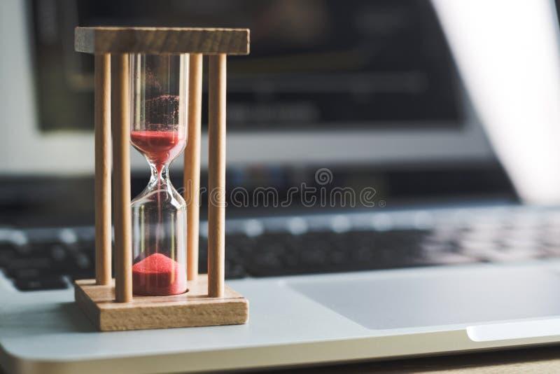Таймер часов песка на ноутбуке символ времени стоковое фото