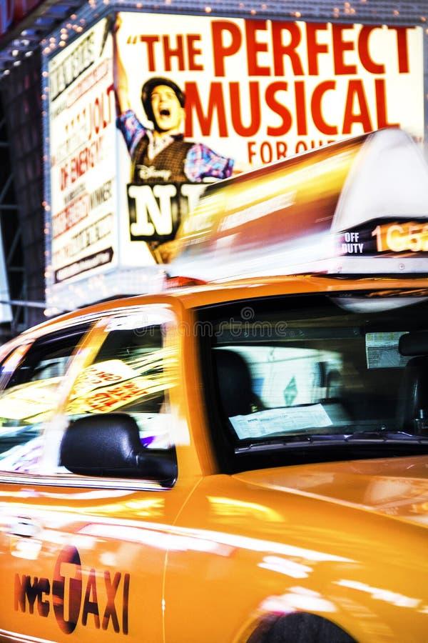 Таймс площадь, Нью-Йорк, Нью-Йорк, Соединенные Штаты - около 2012 - такси управляя в Таймс площадь движения расплывчатом на ноче стоковая фотография