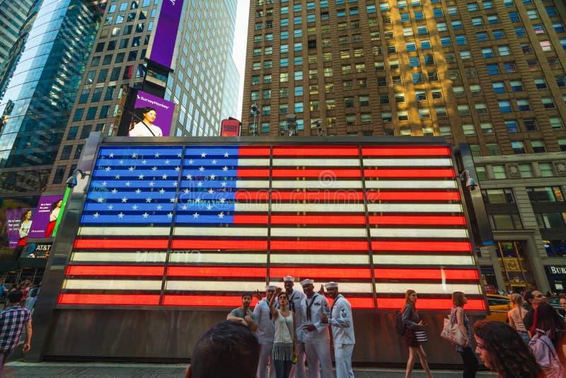 Таймс-сквер Нью-Йорка Неоновый свет американского флага Группа людей принимая фото на Бродвей стоковые изображения