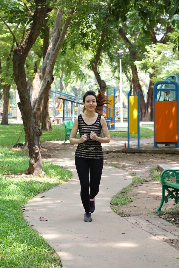 Тайская взрослая красивая девушка делая идущие тренировки в парке стоковая фотография rf