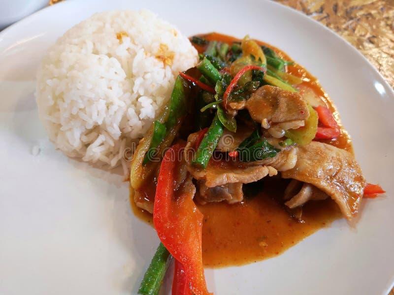 Тайская еда - острую жареную свинину с овощами, поданными рисом на белой тарелке, Pad Prik Kang Mhoo стоковое фото