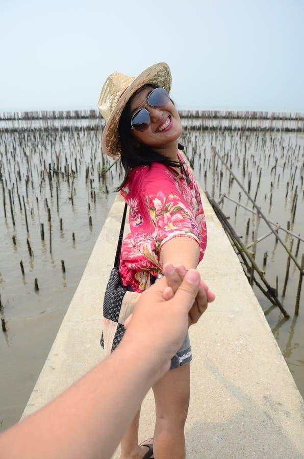 Тайская женщина водит кто-то рукой и держит на мосте дорожки стоковые фотографии rf