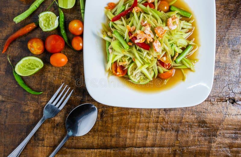 Тайская кухня, салат и томаты папапайи, перцы и condiments на деревянном столе стоковые фотографии rf