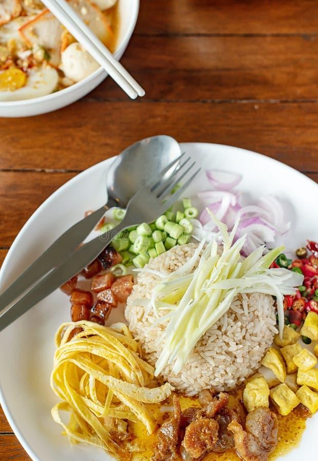 Тайская кухня - Ka Pi Kao Cluk смешал сваренный рис с соусом затира креветки на белом круглом блюде стоковое фото