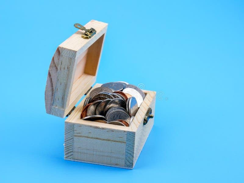 Тайская монетка в деревянном комоде на голубой предпосылке стоковые изображения