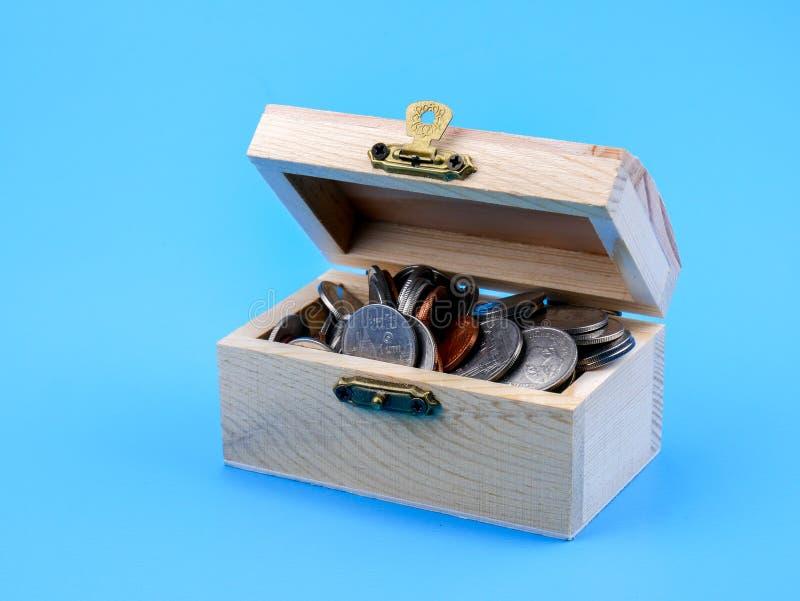 Тайская монетка в деревянном комоде на голубой предпосылке стоковая фотография