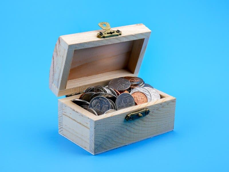 Тайская монетка в деревянном комоде на голубой предпосылке стоковые фотографии rf