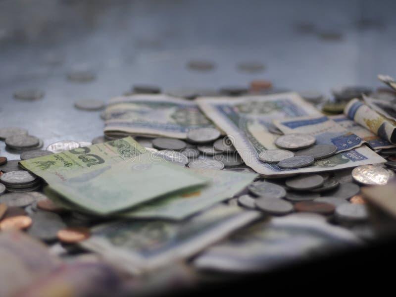 ТАЙСКИЕ банкноты, монетки, и другой взгляд крупного плана урожая валюты в коробке пожертвования стоковые изображения rf