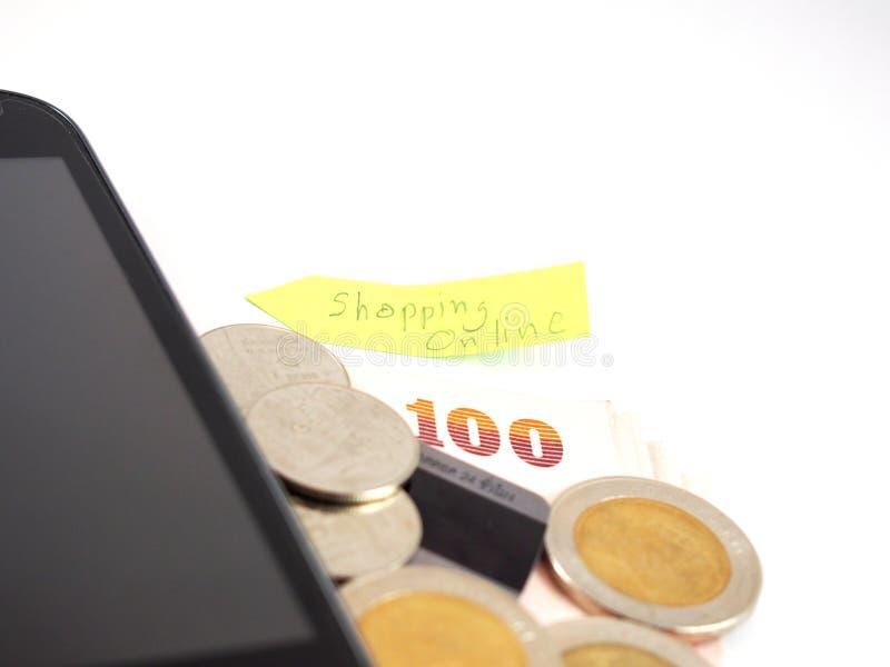Тайские деньги, бат 100 и монетки с кредитной карточкой, черным изолированным мобильным телефоном с онлайн делом покупок на столб стоковые изображения rf