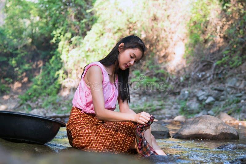 Тайские женщины моя одежды вдоль реки стоковые изображения