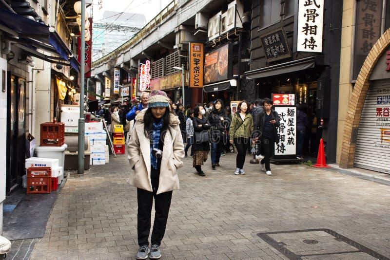 Тайские женщины с японским народом и чужими путешественниками идя перемещение и посещение в рынке Ameyoko на город в Токио, Япони стоковые фотографии rf