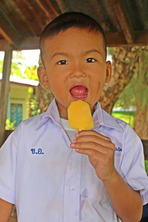Тайский мальчик в форме студента ест мороженое стоковое фото