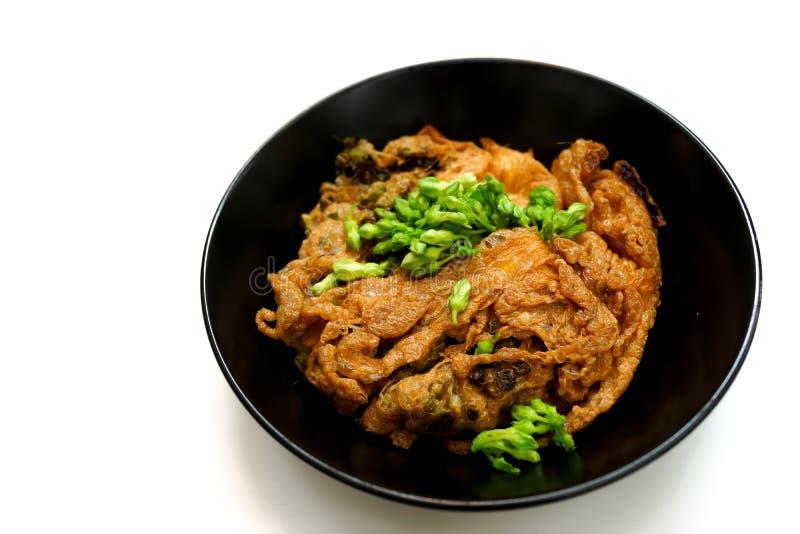 Тайский омлет с зеленым creeper cowslip в черном блюде с белой предпосылкой стоковая фотография